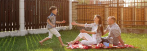 woman and handsome man sit in yard and son jumps on mother