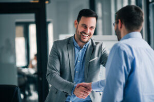 Portrait of cheerful young manager handshake with new employee.